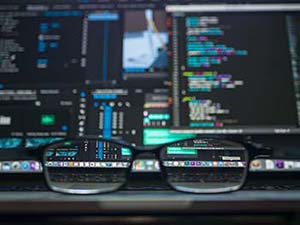 Glasses sitting on a desk in front of a laptop showing diagnostics on the screen